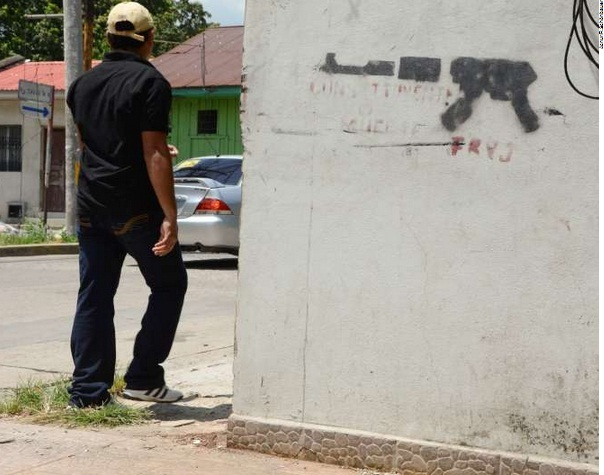 A young man walks past graffiti of a machinegun in San Pedro Sula, the second largest city in Honduras. The city suffers from an extremely high rate of violence with murders committed on a regular basis. Young men are at particular risk.